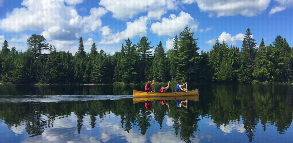 3 campers canoeing in a clear lake with trees in the background