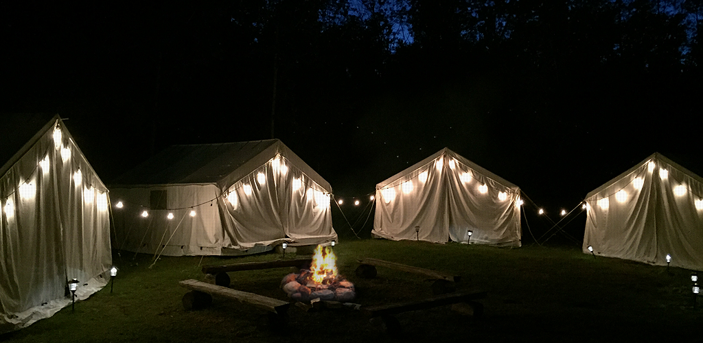 Tim Town at night, with string lights and a lit campfire