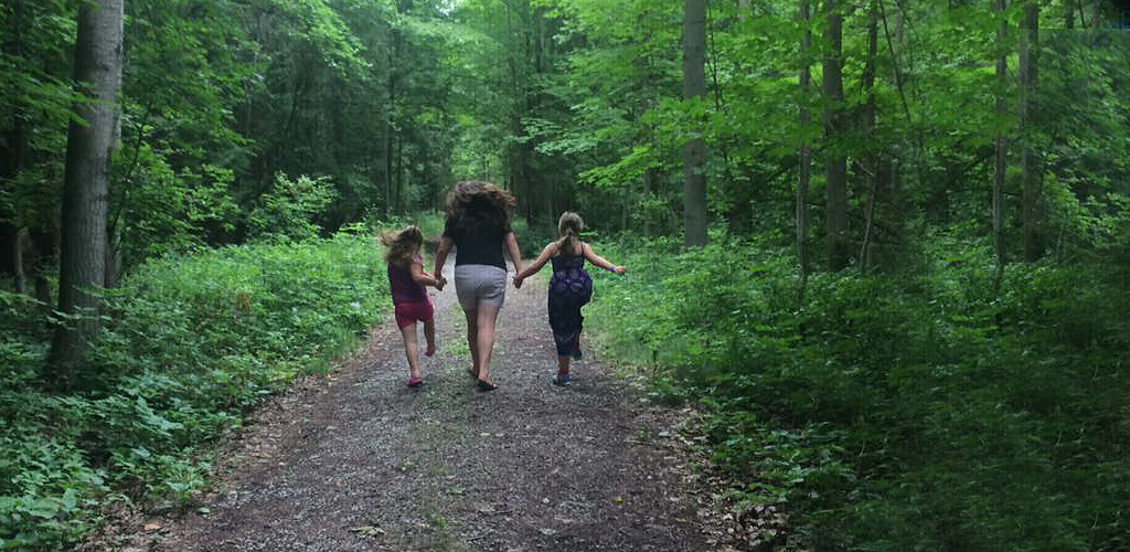 Staff member and two campers walking through the woods