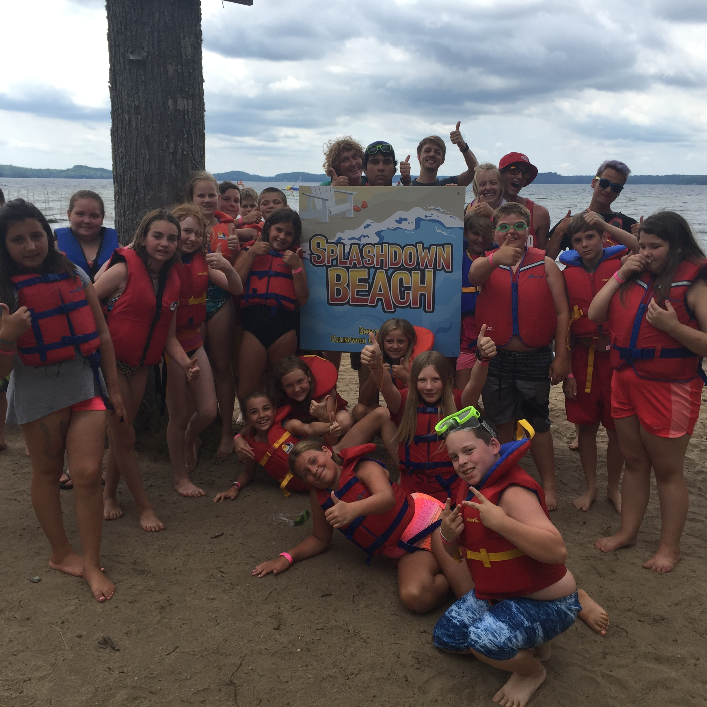 Campers in lifejackets posing on the Newport Beach in front of the Splashdown Beach sign