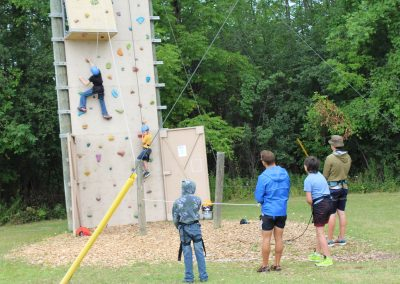 Two Campers Climbing on the rock wall, with staff and campers belaying and watching