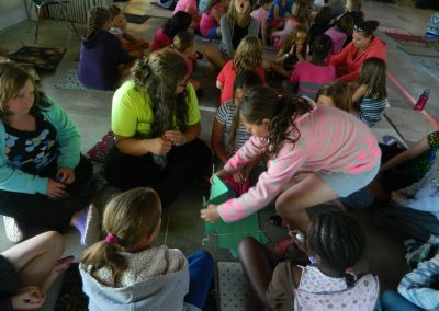 Campers sitting in a circle doing an activity with paper
